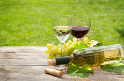 White and red wine glasses and bottle with bunch of grapes Royalty Free Stock Images