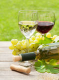 White and red wine glasses and bottle with bunch of grapes Stock Photo