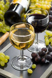 White and red wine in glasses, grapes in the background Stock Images