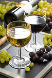 White and red wine in glasses, grapes in the background Royalty Free Stock Photos