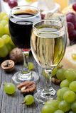 White and red wine, grapes, nuts and cheeses Royalty Free Stock Photos