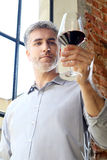 White or red wine? Man pours wine into a glass. Handsome middle-aged man drinking wine Stock Photo