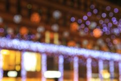 White, red, yellow Blurred lights of the Christmas and New Year illuminations on the background of architecture, abstract bokeh,. White, red, yellow Blurred stock photos