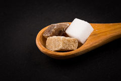 White refined and brown sugar in wooden spoon Royalty Free Stock Photos