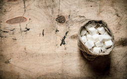 White refined sugar in the bag. On wooden background. Royalty Free Stock Photos