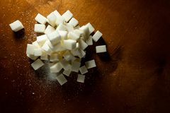 Cubes of white unrefined sugar on a wooden background with light reflections. Cubes white unrefined sugar wooden background light reflections cutting board made royalty free stock photo