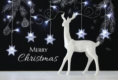 White reindeer on wooden table over chalkboard background with hand drawn chalk illustrations. Stock Photo