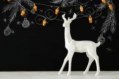 White reindeer on wooden table over chalkboard background with hand drawn chalk illustrations. Royalty Free Stock Images