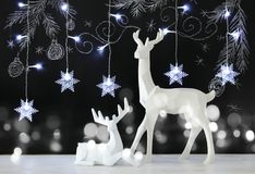 White reindeer on wooden table over chalkboard background with hand drawn chalk illustrations. Stock Image