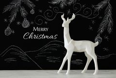 White reindeer on wooden table over chalkboard background whith hand drawn chalk illustrations. Royalty Free Stock Photography