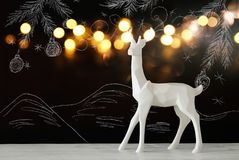 White reindeer on wooden table over chalkboard background whith hand drawn chalk illustrations. Stock Photos