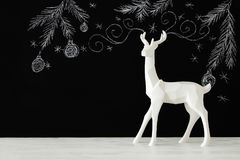 White reindeer on wooden table over chalkboard background whith hand drawn chalk illustrations. Royalty Free Stock Photos