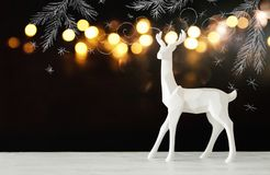 White reindeer on wooden table over chalkboard background whith hand drawn chalk illustrations Royalty Free Stock Image