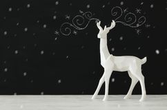 White reindeer on wooden table over chalkboard background whith hand drawn chalk illustrations Royalty Free Stock Images