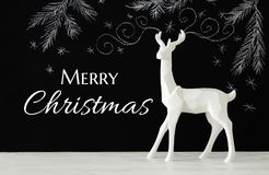 White reindeer on wooden table over chalkboard background whith hand drawn chalk illustrations Stock Photo