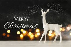 White reindeer on wooden table over chalkboard background whith hand drawn chalk illustrations. Royalty Free Stock Image