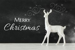 White reindeer on wooden table over chalkboard background whith hand drawn chalk illustrations Royalty Free Stock Photography
