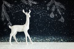 White reindeer on wooden table over chalkboard background whith hand drawn chalk illustrations. Royalty Free Stock Images