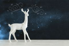 White reindeer on wooden table over chalkboard background whith hand drawn chalk illustrations Royalty Free Stock Photo