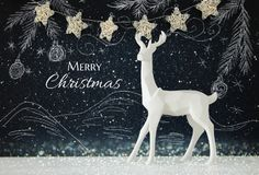 White reindeer on wooden table over chalkboard background whith hand drawn chalk illustrations. Royalty Free Stock Photo