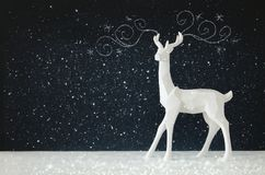 White reindeer on wooden table over chalkboard background whith hand drawn chalk illustrations Stock Photography