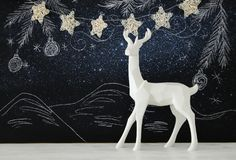 White reindeer on wooden table over chalkboard background whith hand drawn chalk illustrations. Stock Images