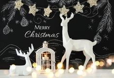 White reindeer on wooden table over chalkboard background whith hand drawn chalk illustrations Stock Images