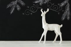 White reindeer on wooden table over chalkboard background whith hand drawn chalk illustrations. Stock Image