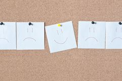 White reminder sticky smile note on cork board Stock Image
