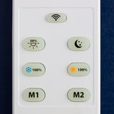 White remote control with the buttons on the blue background stock illustration