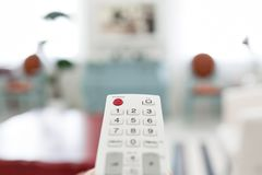 White remote control. Program switching on TV keypad. Bright living room. Morning european home. Using white remote control. Program switching or button Royalty Free Stock Photography