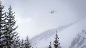 White rescue helicopter flying in heavy snowfall in winter ski resort. In French Alps stock photo