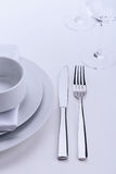 White restaurant table set. Plates, knife, fork and glasses on white tablecloth Stock Photo