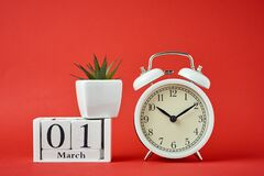 Free White Retro Alarm Clock On Red Background And Wooden Calendar Blocks With Date 1 March On The Red Background. Time Concept Stock Photo - 171996060