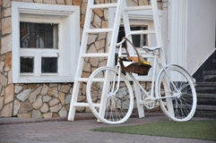 White retro bicycle with basket with bakery products, windows Royalty Free Stock Photo