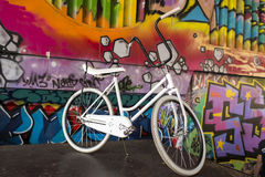 White retro bicycle. White vintage bicycle with graffiti background Stock Image