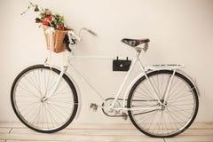 White retro bicycle on white wooden floor Stock Photos