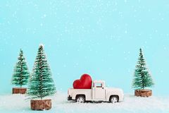 White retro toy car delivering heart for Valentine`s day in toy snowy forest. Symbol of love royalty free stock photo