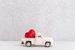 White retro toy car delivering heart for Valentine`s day in toy snowy forest. Symbol of love stock photo