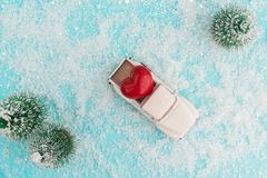 White retro toy car delivering heart for Valentine`s day in toy snowy forest. Symbol of love. Top view royalty free stock photos
