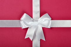 White ribbon bow. White ribbon with bow on a pink background Royalty Free Stock Photography