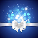 White ribbon and bow on blue background. Royalty Free Stock Images