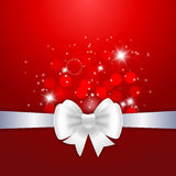 White ribbon and bow on red background. Royalty Free Stock Image