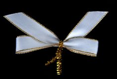White ribbon bow. With a gold border isolated on black background stock photography
