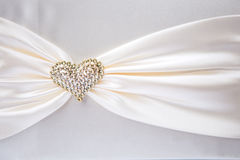 White ribbon with gold heart Stock Images