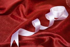 White ribbon on red drape Stock Image