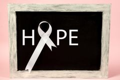 Lung cancer ribbon, white ribbon, a symbol of the fight against lung cancer. The white ribbon, a symbol of the international or world day of fight against lung royalty free stock photography