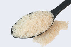 White Rice. In black spoon over white background Royalty Free Stock Images