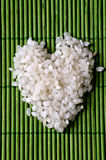 White rice. In shape of a heart on a green background Royalty Free Stock Photo