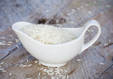 White rice. In a gravy boat on the board Stock Image